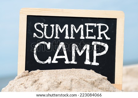 Text Summer camp written with chalk on chalkboard. Text Summer camp written with chalk on chalkboard, on sandy beach side