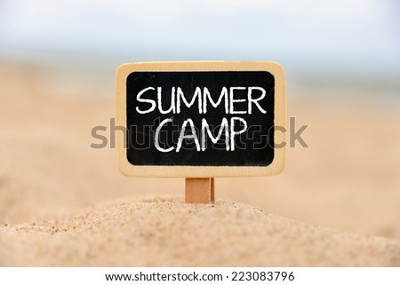 Text Summer camp written with chalk on chalkboard.Text Summer camp written with chalk on chalkboard, on sandy beach side  - stock photo