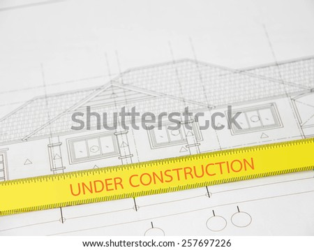 Text ''under construction'' in measuring tape overblurred architectural blueprint of office building - stock photo