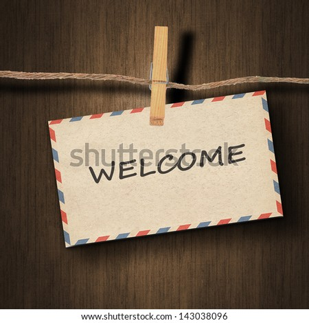 text welcome on the old envelope and clothes peg wood background - stock photo