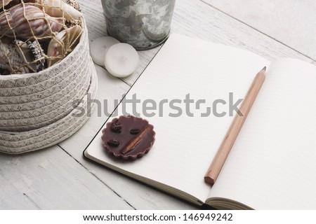Textbook, pen and decoration on a white hardwood table. Write down your plans,ideas,memories and ideas. Studio shot. - stock photo