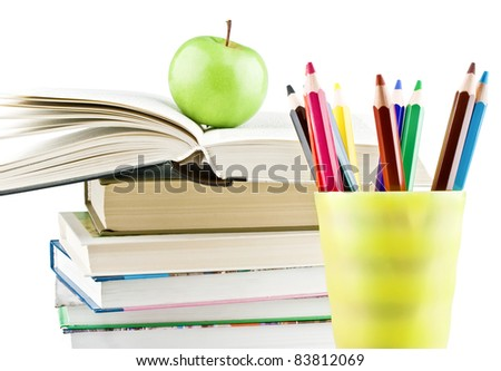 Textbooks with apple on top and multicolor pencils close-up isolated on white