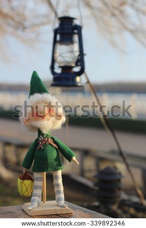 Textile doll gnome in a green jacket and a flashlight in striped socks - stock photo