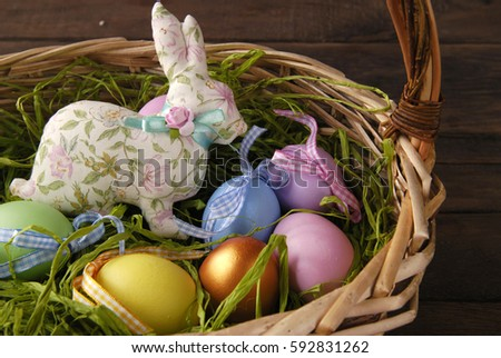 Textile easter bunny and colored eggs in a wicker basket.