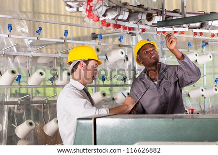 textile factory worker and quality controller checking quality - stock photo