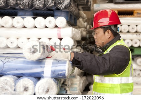 Textile factory worker arranging fabric in warehouse - stock photo