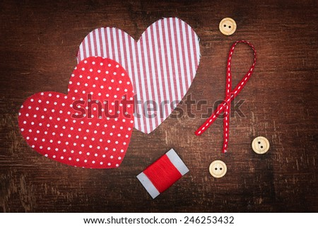 Textile hearts and buttons on old shabby wooden background - stock photo