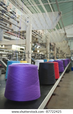 Textile machine weaving with cone fiber with several colors - stock photo