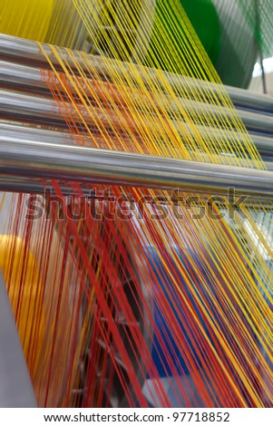 Textile machine with red and yellow colors threads - stock photo