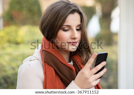 Texting, reading sms. Closeup portrait headshot beautiful young woman girl student looking on mobile phone looking isolated cityscape outdoor background. Multicultural mixt race, asian russian model