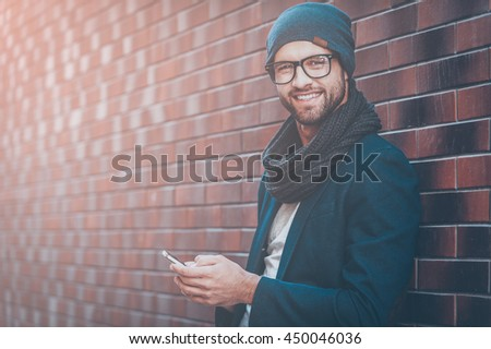 Texting to girlfriend. Handsome young man in smart casual wear holding mobile phone while leaning at the brick wall - stock photo