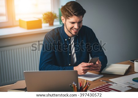 Texting to her. Cheerful young handsome man using his smartphone with smile while sitting at his working place