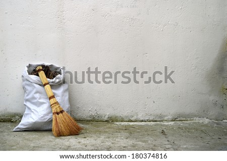 Textural backdrop for text. A bag of garbage and old broom against a white wall - stock photo