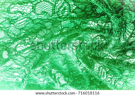 Texture, background, pattern. Cloth green lace. Background of fabric from lace stylized roses. Abstract lace pattern with flowers. Wallpaper, underwear and jewelry. Your invitations