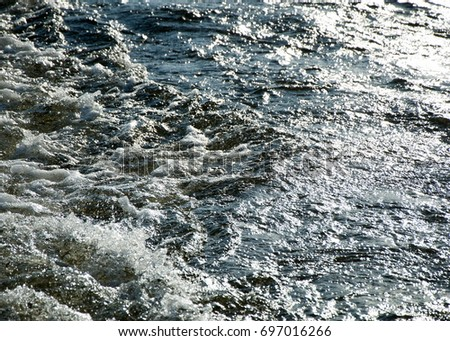 texture. background. water under the setting sun. Background texture of water in storm. the surface of the water flowing under the rays of the setting