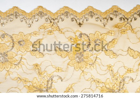 Texture. Lace fabric golden yellow color photos made in the studio. a fine open fabric, typically one of cotton or silk, made by looping,  - stock photo