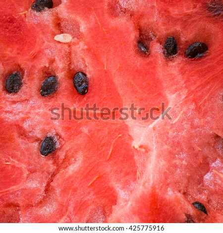 Texture of a ripe red watermelon with seeds close up as a background