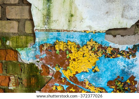 Texture of an old damaged white brick wall with crumbling plaster and peeling colorful paint - stock photo