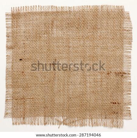 texture of Burlap hessian square with frayed edges on white background - stock photo