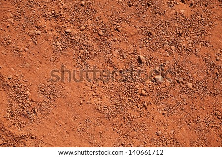Texture of dry red clay with stones close-up - stock photo