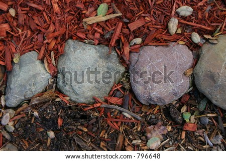 Texture of large repeating stones on on wood-chip ground