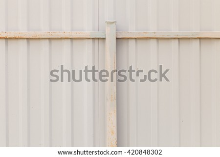 Texture of metal fence picket Profile decking with a rusty rack bar. Internal primed side of a metal picket fence with corrosion of the upper guide bar and the support pillar pole - stock photo