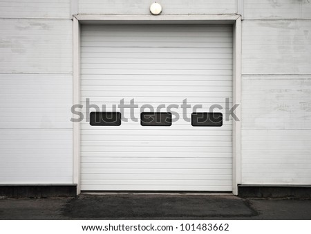Texture of modern storage building wall with closed gate - stock photo