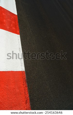Texture of motor race asphalt and red white curb. Close up on Grand Prix street circuit - stock photo