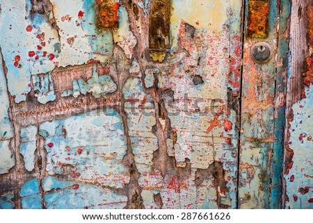 texture of old wooden door with crumbling paint layers - stock photo