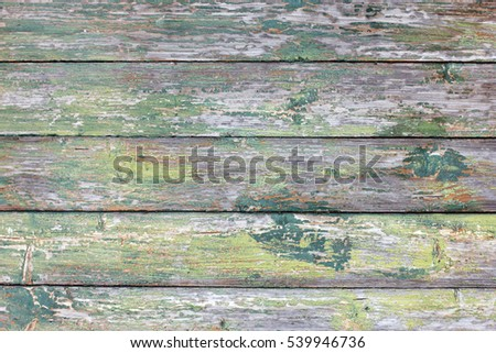 texture of old wooden grey and green painted planks  with peeling paint closeup