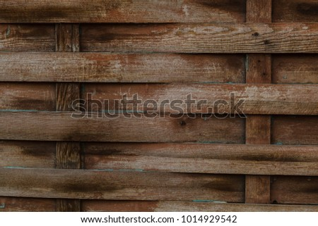 Texture of old wooden wicker fence with stains of paint.