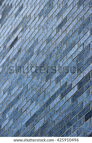 Texture of vertical diagonal blue and gray brick wall