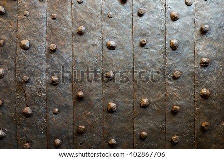 Texture of vintage metal with rivets. Metal plate or armor background with rivets. Old castle medieval grunge pattern. - stock photo