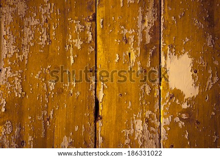 Texture of weathered wooden lining boards with peeling yellow paint and rusty nail heads. Shadowed angles. - stock photo