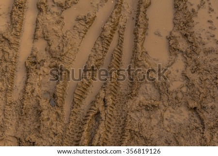 Texture of wet brown mud with bicycle tyre tracks - stock photo