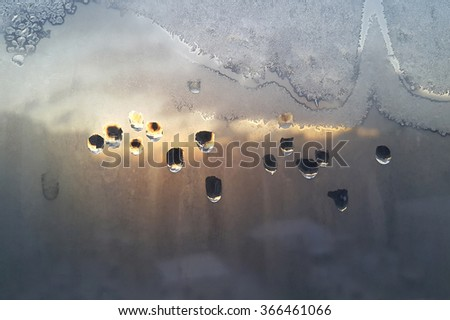 Texture of window glass with water drops, ice pattern and sunlight - stock photo