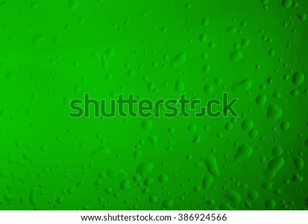 Texture water drops on the green bottle close-up as a background. - stock photo