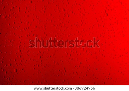 Texture water drops on the red bottle close-up as a background. - stock photo