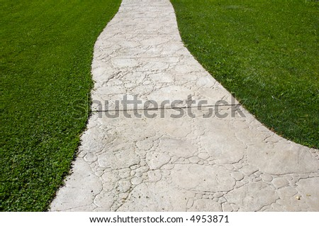textured cement pathway meandering through lush grass