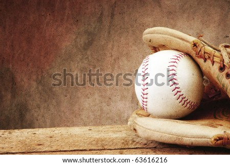 Textured for antique look Baseball/softball with mit on old wood table and tan aged background with copy space - stock photo