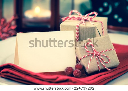 Textured greeting card with copyspace for your own text on a plate with wrapped Christmas presents as a concept of a festive dinner with retro vintage filter effect - stock photo