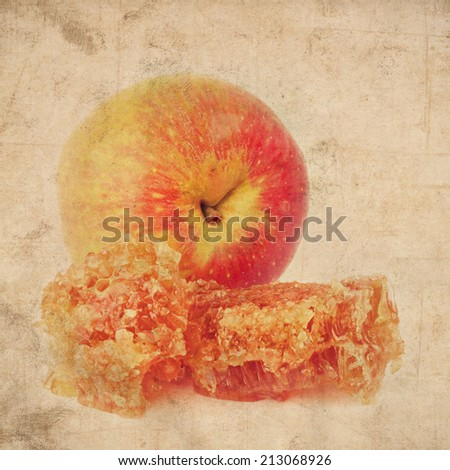 Textured old paper background with sweet honey comb with honey and apple fruit - Jewish traditional food for the holiday of Rosh Hashana (Jewish new year). Vintage style image - stock photo