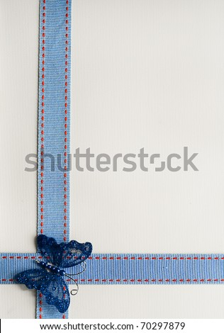 Textured ribbon over cream textured paper with butterfly sequin. - stock photo