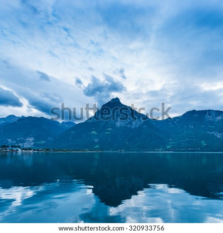 Textured sky over the mountain range is reflected in the surface of the lake. - stock photo