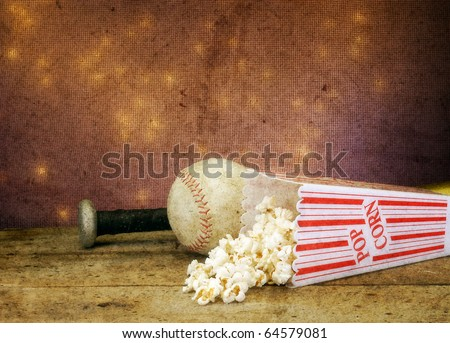 Textured soft focus baseball bat, ball, and popcorn on vintage table with bokeh antique feel - stock photo