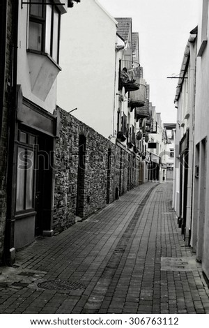 Textured stoned road of medieval backstreet in Cork town, Ireland. Black and white filtered - stock photo