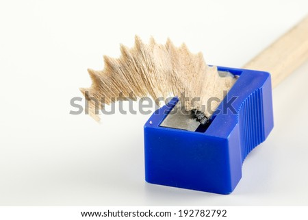 Textured wood shaving in a pencil sharpener with graphite from sharpening the accompanying wooden pencil on a white background conceptual of an office or school. - stock photo