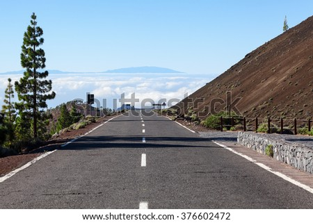 TF-38 driveway is connecting the Teide volcano and Vilaflor village on Tenerife island. High mountain asphalt road is over clouds - stock photo