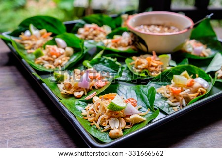 "Thai appetizer called ""Miang Kham"", some of nutritious snack wrapped in leaves with a sweet and salty sauce. - stock photo"