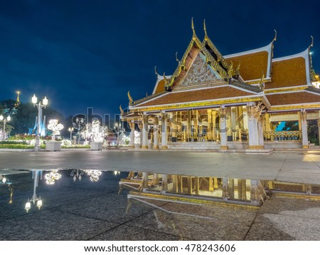 Thai art pavilion in public outdoor square in Bangkok with water reflection, under twilight evening sky